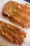 Raw pork belly with spices mixture. On a plastic board Royalty Free Stock Photos