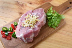 Raw pork on board and vegetables. On wood background Royalty Free Stock Photo