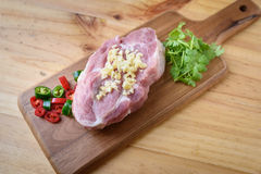 Raw pork on board and vegetables. On wood background Royalty Free Stock Images