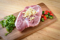 Raw pork on board and vegetables. On wood background Stock Photos