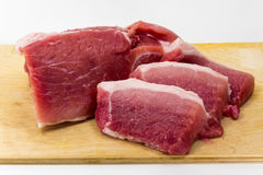Raw pork on the Board on a white background. A piece of juicy pork baked on a wooden board Stock Photos