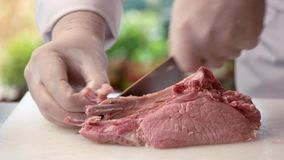 Raw pork with bone. Chef`s hands with a knife. Cook a perfect steak stock video