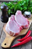 Raw pork chop on the bone with parsley, mint, pepper and sea salt Royalty Free Stock Photos