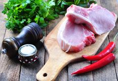 Raw pork chop on the bone with parsley, mint, pepper and sea salt Royalty Free Stock Image