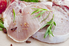 Raw pork chop fillets with spices. Fresh pork chop slices with dry peppers, mustard, tarragon leaves and vegetables Stock Image