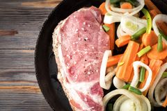Raw pork chop marinated meat roll with assorted vegetables. Raw pork chop marinated meat roll with coarse sea salt pepper assorted vegetables with carrots green Royalty Free Stock Images