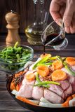 Raw pork chop marinated meat roll with assorted vegetables. Raw pork chop meat roll wrapped with twine jute marinated pour soy sauce olive oil with coarse sea Royalty Free Stock Photos