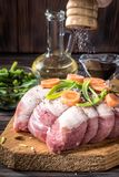 Raw pork chop marinated meat roll with assorted vegetables. Raw pork chop meat roll wrapped twine jute marinated strew coarse sea salt shaker mill olive oil with Stock Photo