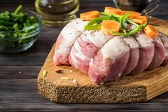 Raw pork chop marinated meat roll with assorted vegetables. Raw pork chop marinated meat roll wrapped with twine made of jute, with coarse sea salt, pepper Royalty Free Stock Photo