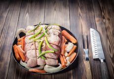 Raw pork chop marinated meat roll with assorted vegetables. Raw pork chop marinated meat roll with coarse sea salt pepper assorted vegetables with carrots green Royalty Free Stock Photos