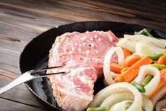 Raw pork chop marinated meat roll with assorted vegetables. Raw pork chop marinated meat roll with coarse sea salt pepper assorted vegetables with carrots green Royalty Free Stock Photography