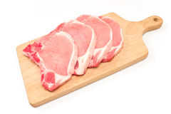 Raw pork chop meat on cutting board isolated on white. Background Stock Photos