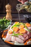 Raw pork chop marinated meat roll with assorted vegetables. Raw pork chop meat roll wrapped with twine jute marinated pour olive oil with coarse sea salt pepper Royalty Free Stock Images