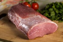 Raw pork chop meat on wooden cutting board. With parsley and tomatoes in background Stock Photo