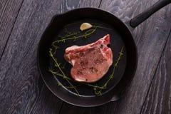 Raw pork chop in pan Royalty Free Stock Image