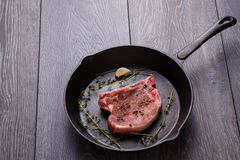 Raw pork chop in pan Royalty Free Stock Images