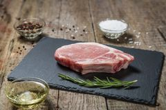 Raw pork chop with pepper and salt on a stone serving Board. Raw pork chop with pepper and salt on stone serving Board on old wooden table Royalty Free Stock Photography