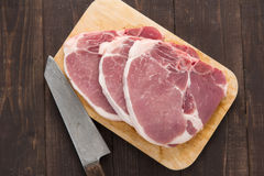 Raw pork chop steak and cleaver on wooden background Stock Photos