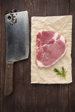Raw pork chop steak and cleaver on wooden background Stock Photography