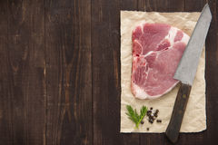 Raw pork chop steak and cleaver on wooden background Royalty Free Stock Photo
