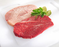 Raw pork chop and steak on cutting board. Stock Images