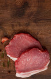 Raw pork chop steak and garlic, pepper on the brown wooden table background. rustic kitchen table with copy space. Top view Royalty Free Stock Images