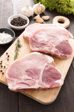 Raw pork chop steak and garlic, pepper on wooden background.  Stock Photography