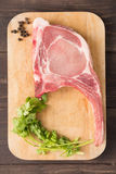 Raw pork chop steak and pepper, vegetable on wooden background.  Stock Photography