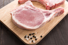Raw pork chop steak and salt, pepper on wooden background.  Stock Images