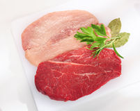 Raw pork chop and steak on white cutting board. Stock Image