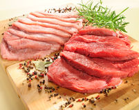 Raw pork chop and steaks for barbecue. On a cutting board stock photo