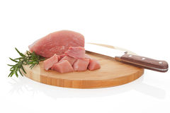 Raw pork on chopping board. Raw pork piece with fresh rosemary and knife on round wooden kitchen board on white background. Culinary meat eating Royalty Free Stock Images