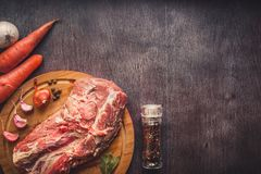 Raw pork on a chopping board on a dark wooden surface and spice for cooking. Food background with copy space. Toned. Still life. Flat lay Stock Image