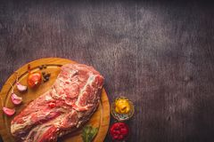 Raw pork on a chopping board on a dark wooden surface and spice for cooking. Food background with copy space. Toned. Still life. Flat lay Royalty Free Stock Image
