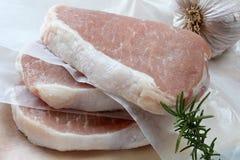 Raw Pork Chops. Three raw pork chops with garlic and rosemary Royalty Free Stock Photos