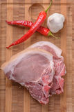 Raw pork chops on the cutting board. With some chili and garlic Stock Images