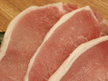 Raw pork chops on cutting board. Thick pork cut, for saute Stock Photo