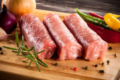Raw pork chops. On cutting board and vegetables Royalty Free Stock Images