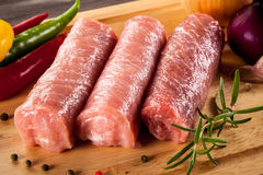 Raw pork chops. On cutting board and vegetables Stock Images