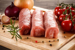 Raw pork chops. On cutting board and vegetables Stock Photos