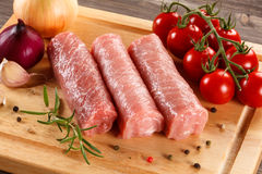 Raw pork chops. On cutting board and vegetables Stock Image