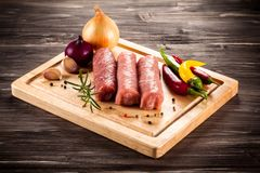 Raw pork chops on cutting board and vegetables. On wooden table Stock Image