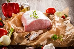 Raw pork chops on cutting board and vegetables. Raw pork on cutting board and vegetables on wooden background Royalty Free Stock Photography