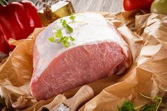 Raw pork chops on cutting board and vegetables. Raw pork on cutting board and vegetables on wooden background Stock Image