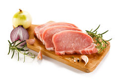 Raw pork chops on cutting board and vegetables Stock Image