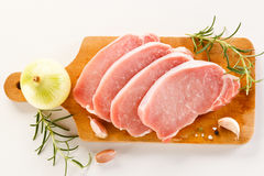 Raw pork chops on cutting board and vegetables Stock Images