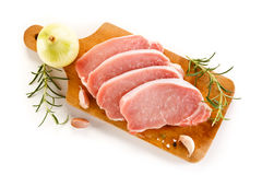 Raw pork chops on cutting board and vegetables Royalty Free Stock Photos