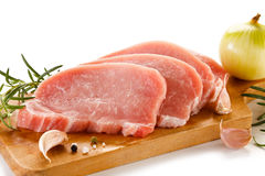 Raw pork chops on cutting board and vegetables Royalty Free Stock Images
