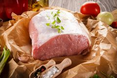 Raw pork chops on cutting board and vegetables. Raw pork on cutting board and vegetables on wooden background Royalty Free Stock Image