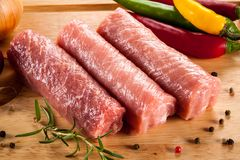 Raw pork chops on cutting board and vegetables. On wooden table Royalty Free Stock Images